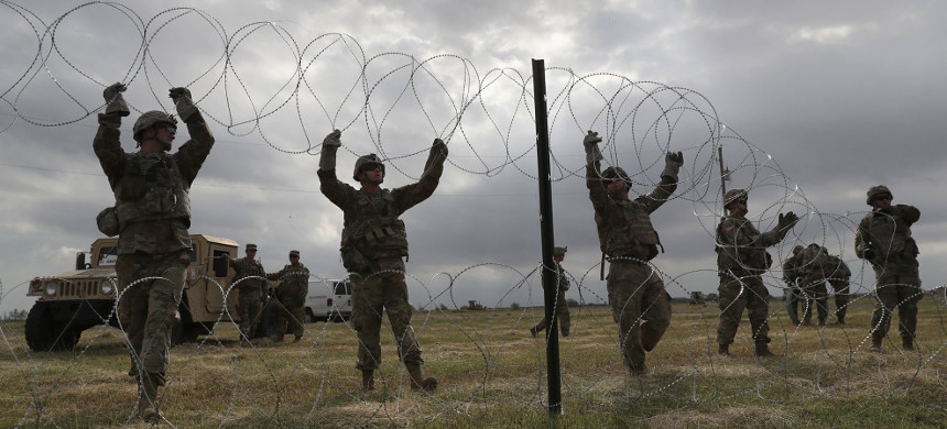 Soldiers from Fort Riley, Kansas, string razor wire near the port of entry at the U.S.-Mexico border, November 4, 2018, in Donna, Texas. (photo: John Moore/Getty)