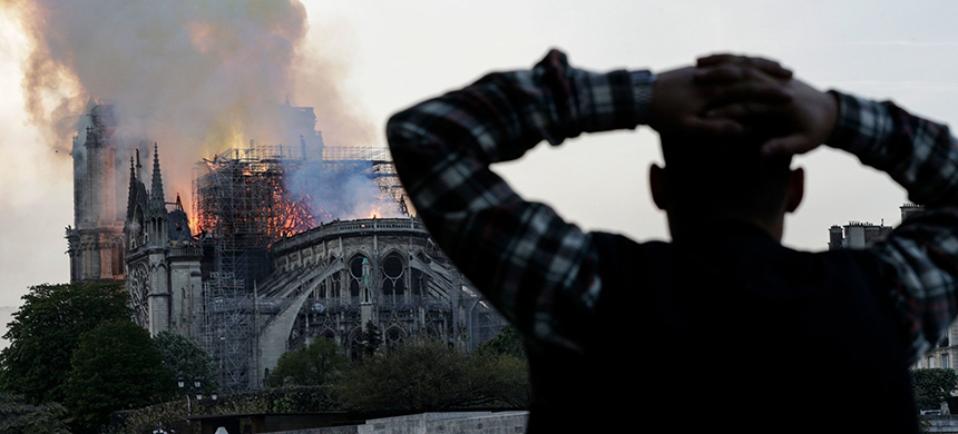 A man watches the landmark Notre-Dame Cathedral burn in central Paris on Monday. (photo: Geoffroy Van Der Hasselt/Getty Images)