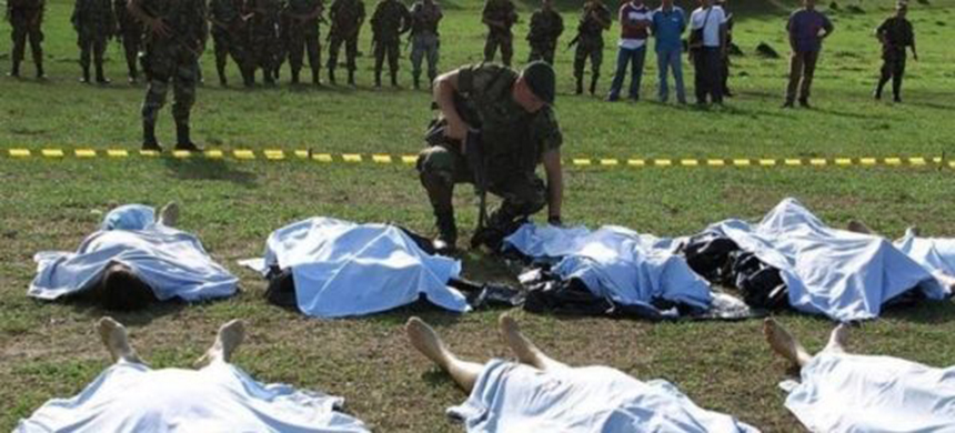 A Colombian soldier looks at the bodies of FARC rebels killed in combat in La Plata, Huila province, July 12, 2002. (photo: Reuters)
