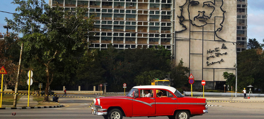 A vintage American car passes beneath a mural of Che Guevara in Revolution Square in Havana, Cuba. (photo: Phil Noble/Reuters)