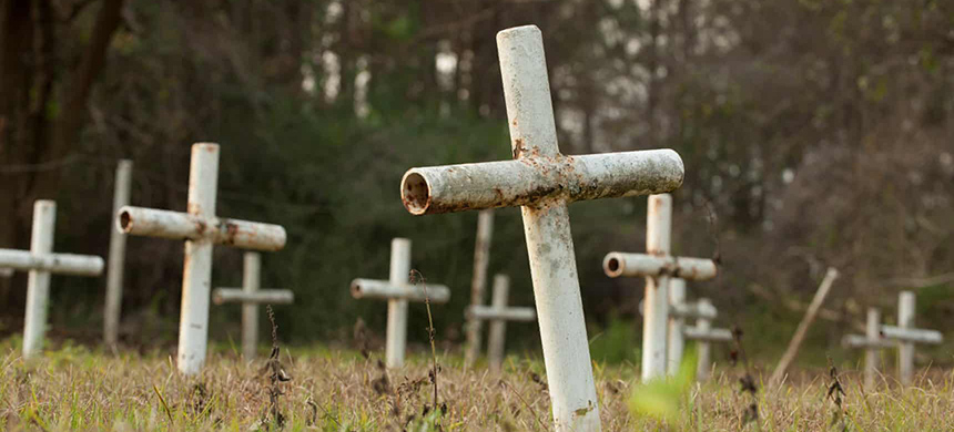 White metal crosses mark graves at the cemetery. (photo: Michael Spooneybarger/Reuters)