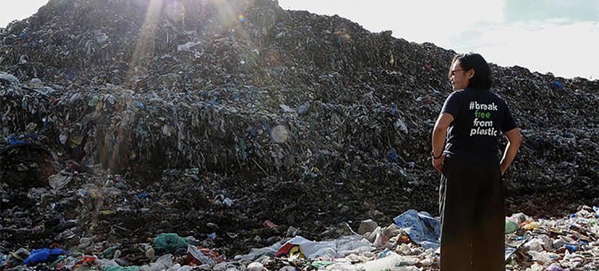 Activist Merci Ferrer stands and looks at the mountain of trash at a dumpsite in Dumaguete City, Philippines. (photo: Greenpeace)