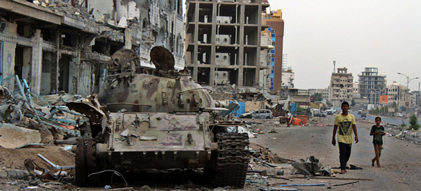 Young Yemenis walk past a tank destroyed in clashes between Houthi and opposition forces in the southern port city of Aden, Yemen. (photo: EPA)