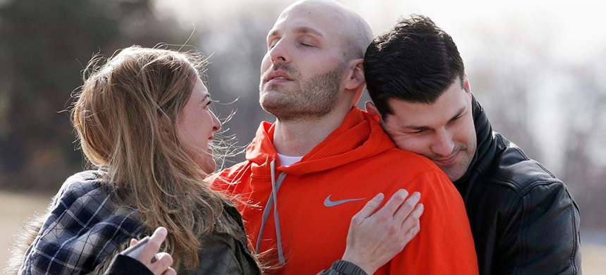 Michael Behenna, center, is embraced by his brother Brett and girlfriend, Shannon Wahl, after his release from prison in Leavenworth, Kansas, in 2014. The White House announced Monday that President Trump had pardoned Behenna, a former soldier convicted of killing an Iraqi prisoner. (photo: Sarah Phipps/AP)