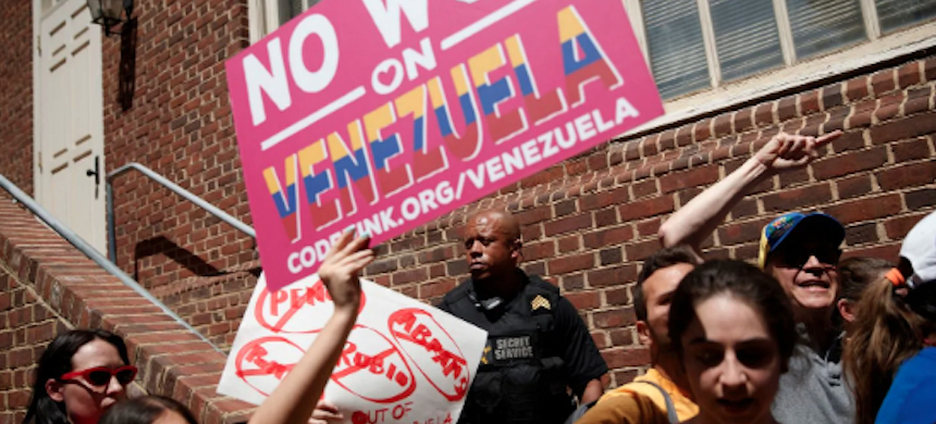 A Secret Service officer watches as supporters of Venezuelan opposition leader Juan Guaidó block Code Pink activists from entering the Venezuelan Embassy in Washington on May 2. (photo: Shawn Thew/EPA-EFE)