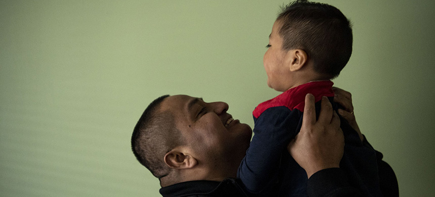 Juan Quintero lifts his son Liam in the air in his home in New York. (photo: Getty Images)