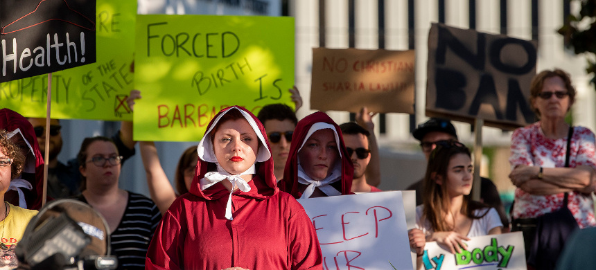 Margeaux Hartline, dressed as a handmaid, protests against a ban on nearly all abortions outside the Alabama State House in Montgomery, Alabama. (photo: Mickey Welsh/AP)