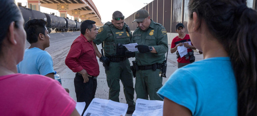 U.S. Customs and Border Protection agents check documents of a small group of migrants, who crossed the Rio Grande from Juarez, Mexico, on May 16, 2019, in El Paso, Texas. (photo: Paul Ratje/Getty)