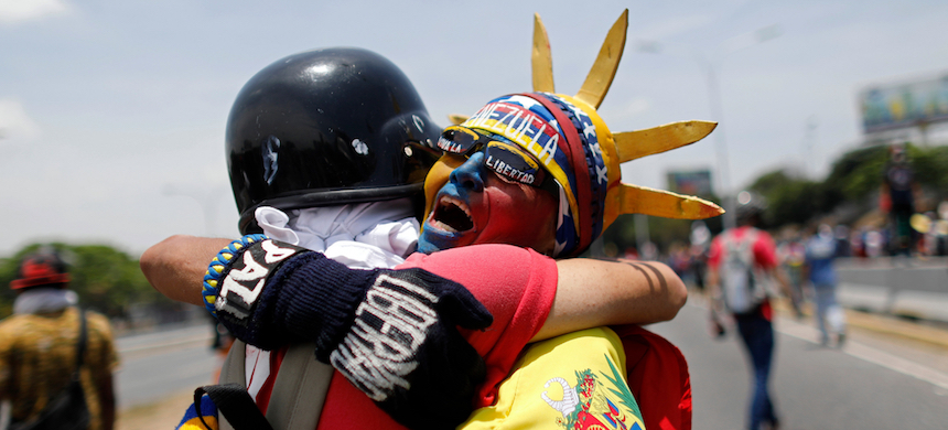 An anti-government protester dressed as Lady Liberty, wearing the colors of Venezuela's flag, hugs a fellow protester during a demonstration near La Carlota airbase in Caracas, Venezuela. Opposition leader Juan Guaidó is calling for Venezuelans to fill streets around the country Wednesday to demand President Nicolás Maduro's ouster. Maduro is also calling for his supporters to rally. (photo: Ariana Cubillos/Shutterstock)