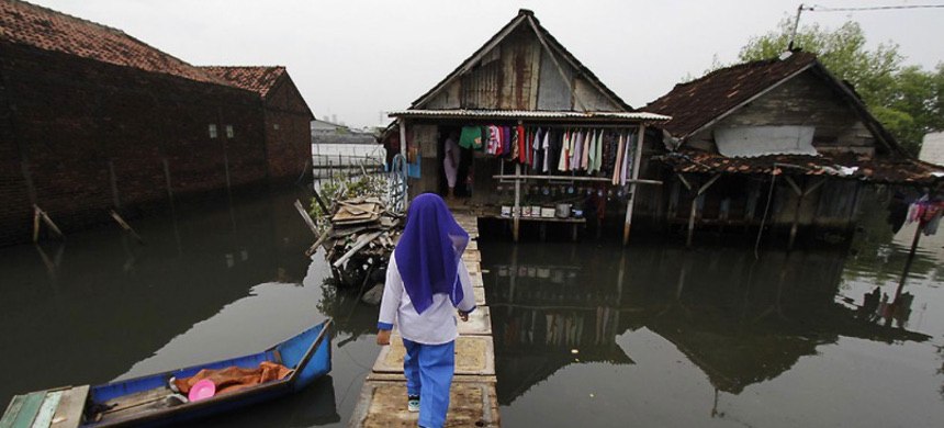 A woman walks in front of her water-logged home in Sriwulan village, Sayung sub-district of Demak regency, Central Java, Indonesia, February 2, 2018. (photo: Siswono Toyudho/Getty)