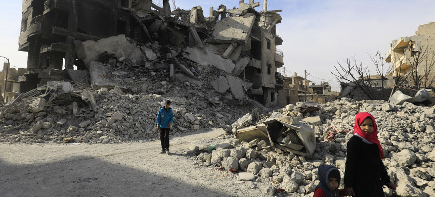Syrians walk amid the debris of destroyed buildings in Raqqa on Jan. 11, 2018. (photo: Delil Souleiman/AFP/Getty)