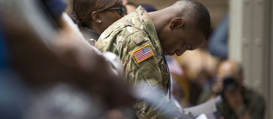 U.S. Army Specialist Shane Cardel, originally from Jamaica, bows his head after taking the Naturalization Oath of Allegiance at a ceremony in New York in late June. (photo: Michael Noble Jr./AP)