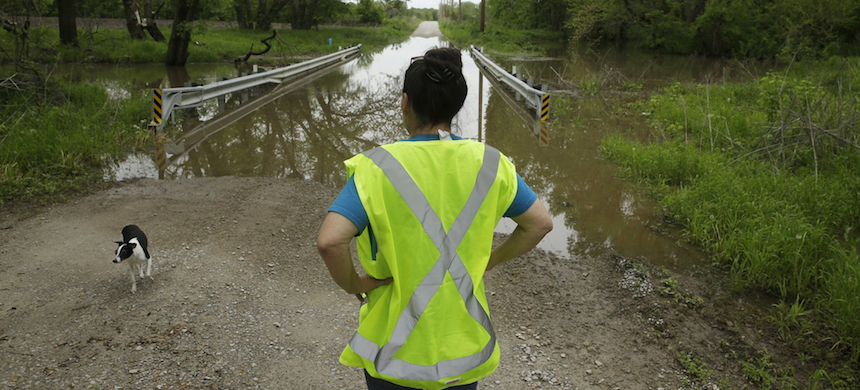 In this photo taken May 8, 2019, Tammy Kilgore as part of her duties with the local volunteer fire department, checks high water covering a road leading to the small community of Mosby, Missouri. 'The floods, I'm tired of dealing with them, I really am,' she said. (photo: Charlie Riedel/AP)