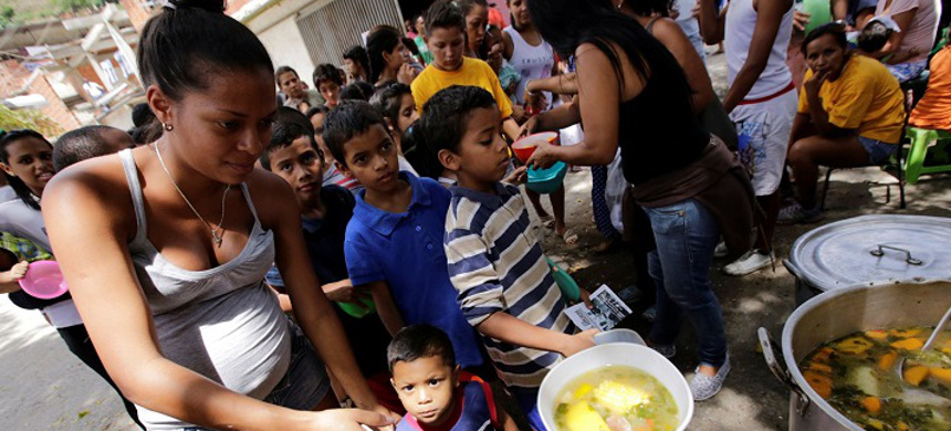 Children queue as they wait to receive free food which was prepared by residents and volunteers on a street in the low-income neighborhood of Caucaguita in Caracas, Venezuela. (photo: Henry Romero/Reuters)