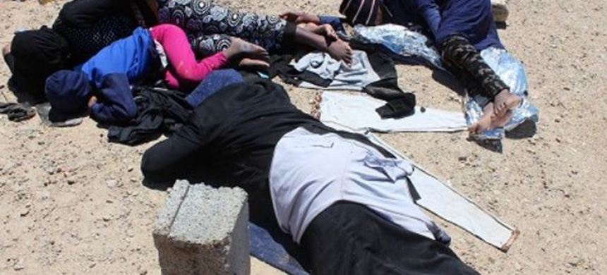 Migrants are seen lying on the ground after they were rescued by a coast guard patrol from a boat accident off the Libyan coast, in Qarabulli, east of Tripoli. (photo: Reuters)