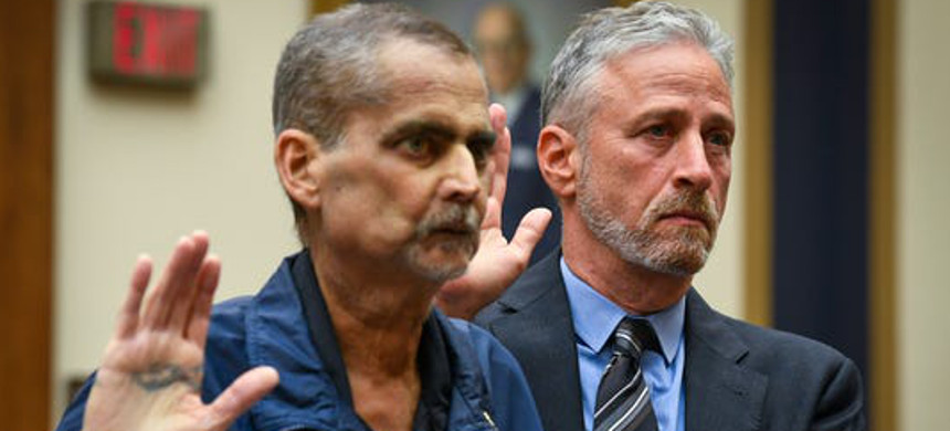 Jon Stewart helps Luis Alvarez, a retired Detective and 9/11 Responder with the New York Police Department. (photo: Unknown)