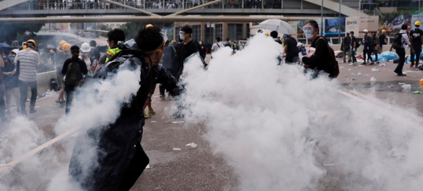A protester throws a tear gas canister during Wednesday's demonstration. (photo: Tyrone Slu/Reuters)