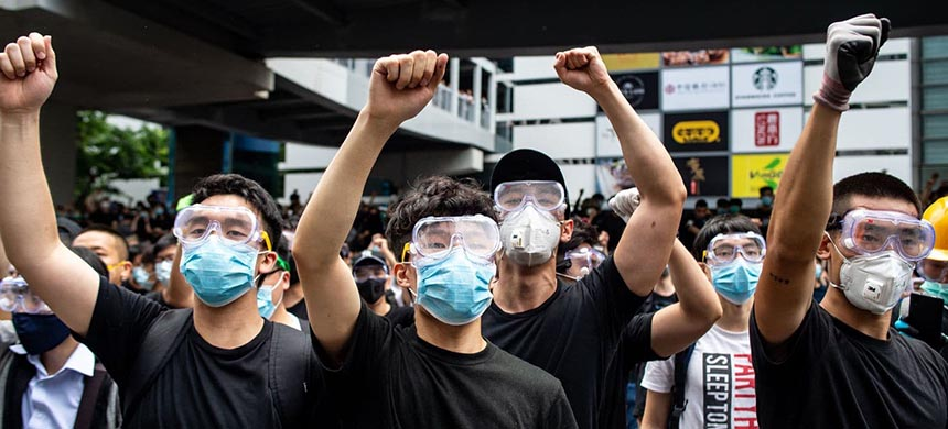 Protesters in masks and goggles chant slogans outside the Legislative Council in Hong Kong on Wednesday. (photo: Philip Fong/AFP/Getty Images)