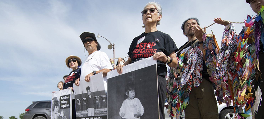 Satsuki Ina (right) and other Japanese Americans who were held in an internment camp as a child, hold photos of themselves, during a protest Saturday at Fort Sill. (photo: J. Pat Carter/Getty Images)