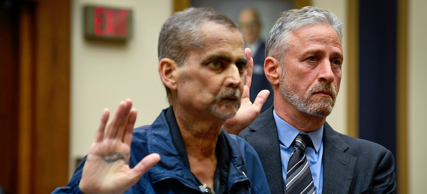 Jon Stewart helps Luis Alvarez, Detective (Ret.) and 9/11 Responder, New York Police Department, as they are sworn before testimony in front of the House Judiciary Committee on the need to reauthorize the September 11th Victim Compensation Fund on June 11, 2019, in Washington. (photo: Jack Gruber/USA TODAY)