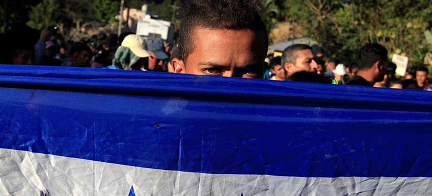 A Honduran, part of a new caravan of migrants traveling to the United States, looks from behind a Honduras flag as he waits to cross into Guatemala at the Agua Caliente border checkpoint in the municipality of Ocotepeque, Honduras. (photo: Jorge Cabrera/Reuters)