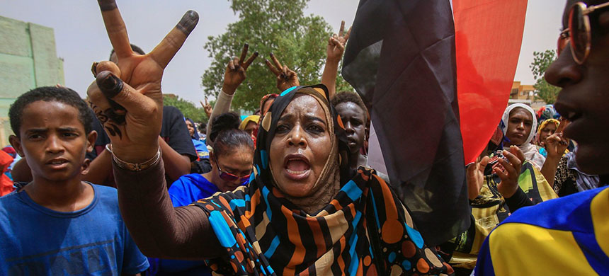 Sudanese protesters flash the V-sign during a mass demonstration in Khartoum on Sunday against Sudan's ruling generals. (photo: Ashraf Shazly/AFP/Getty Images)