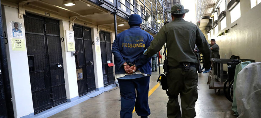 An armed California Department of Corrections and Rehabilitation officer escorts a condemned inmate at San Quentin State Prison's death row on August 15, 2016. (photo: Justin Sullivan/Getty Images)