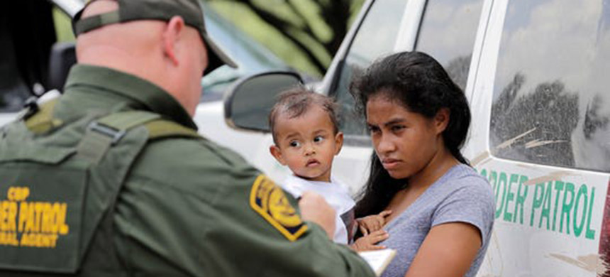 In this June 25, 2018, file photo, a mother migrating from Honduras holds her 1-year-old child while surrendering to U.S. Border Patrol agents after illegally crossing the border near McAllen, Texas. (photo: David J. Phillip/AP)