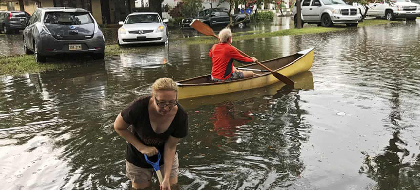People cope with the aftermath of severe weather in the Broadmoor neighborhood in New Orleans, Louisiana, on 10 July. (photo: Nick Reimann/AP)