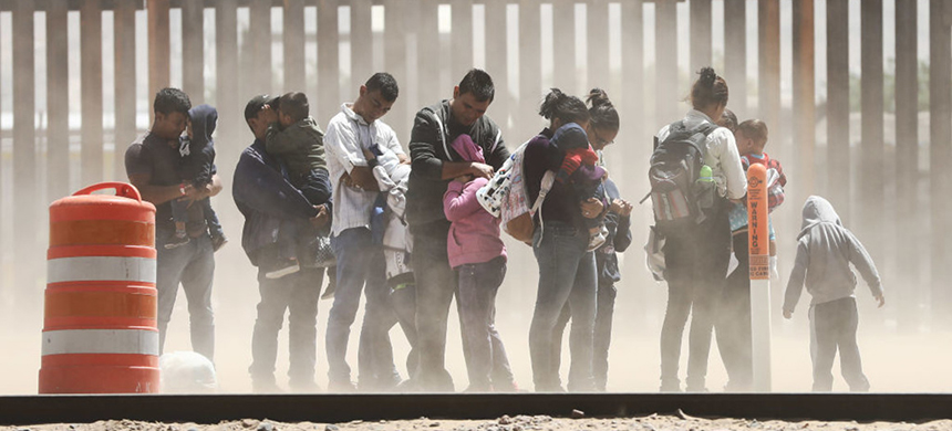 Migrants shield themselves from dust while being detained after crossing to the U.S. side of the U.S.-Mexico border barrier in May in El Paso, Texas. (photo: Mario Tama/Getty Images)