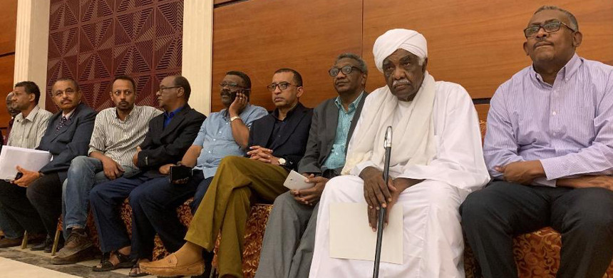 Members of protest movement Alliance for Freedom and Change attend the inking of an agreement between the Sudanese deputy chief of the ruling miliary council and a protest leader in Khartoum early on July 17, 2019. (photo: AFP)