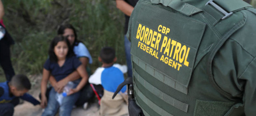 Central American asylum seekers wait as U.S. Border Patrol agents take them into custody on June 12, 2018, near McAllen, Texas. (photo: Getty)