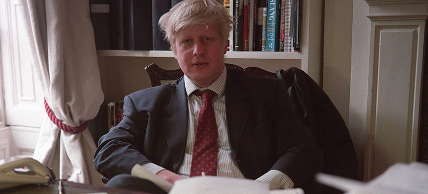 A younger Boris Johnson in his office, with bound volumes of the Spectator magazine behind him. (photo: Neville Elder/Corbis/Getty Images)