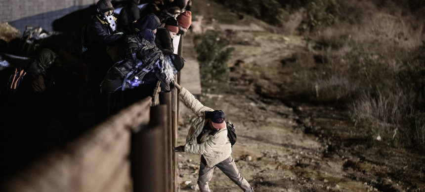 A migrant jumps the border fence at San Diego/Tijuana to get into the U.S. on Jan. 1, 2019. (photo: Daniel Ochoa de Alza/Ap)