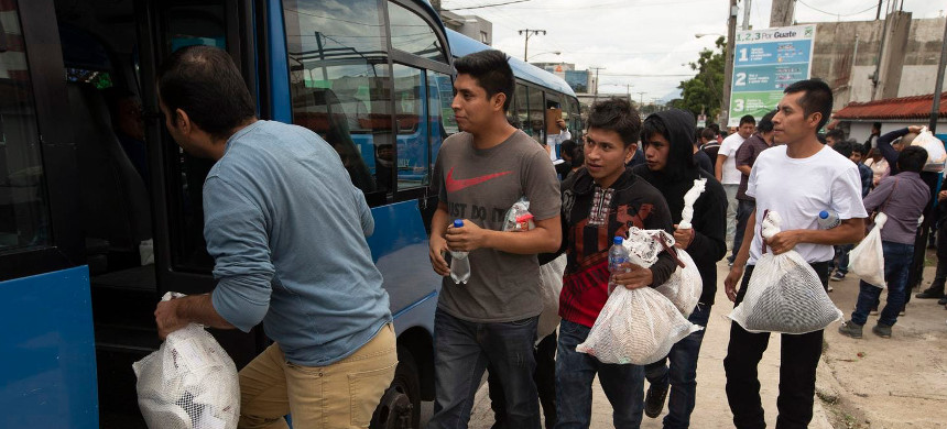 Guatemalan men who were deported from the United States board a bus after arriving at the Air Force Base in Guatemala City on Tuesday, July 16, 2019. (photo: Moises Castillo/AP)