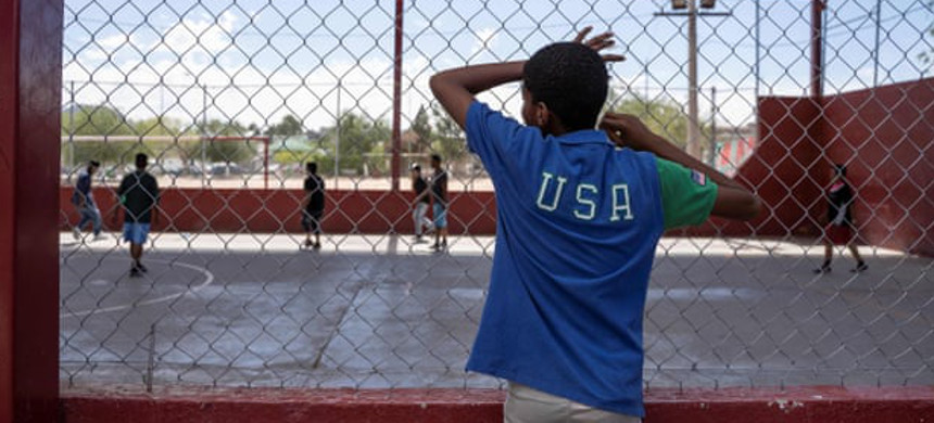 A resident of a migrant shelter watches a soccer match at a nearby park on 9 June. (photo: Paul Ratje/Getty)