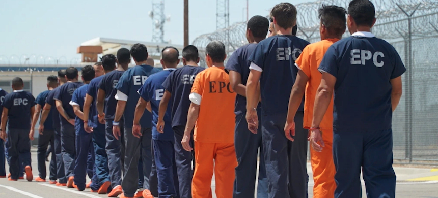 About two dozen detainees were escorted across a courtyard by contract security guards. Blue uniforms are worn by detainees with no criminal history. Orange uniforms are for inmates previously arrested in the U.S. (photo: Jesse Seidman/VICE)