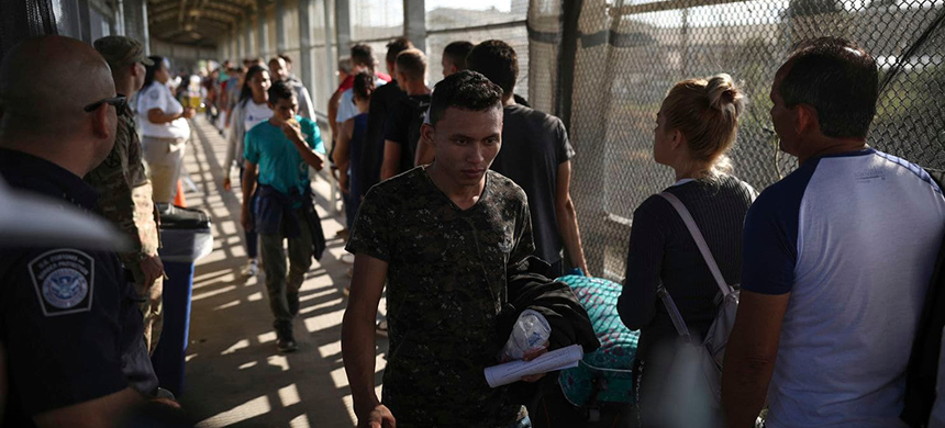 Migrants return to Mexico last week as 15 other migrants line up on their way to request asylum in the United Sates, at the foot of the Puerta Mexico bridge that crosses into Brownsville, Texas, from Matamoros, Mexico. (photo: Emilio Espejel/AP)