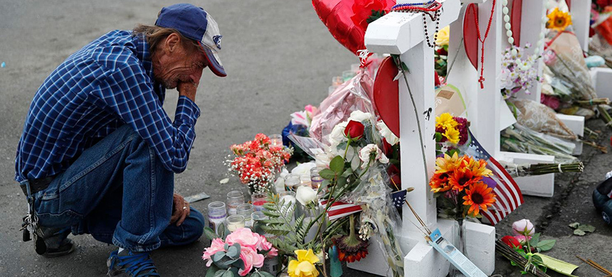 Antonio Basco cries beside a cross at a makeshift memorial near the scene of the mass shooting in El Paso, Texas. (photo: John Locher/AP)