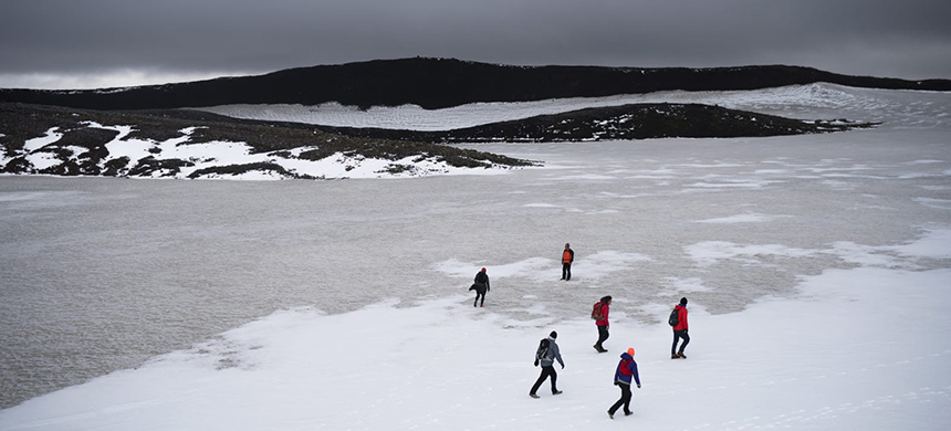 People walk on snow atop the Ok volcano crater on their way to a ceremony for the Okjökull glacier. (photo: Felipe Dana/AP)