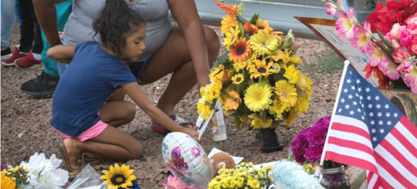 Members of a family place flowers at a memorial outside the Walmart at Cielo Vista Mall in El Paso, where 22 people were killed by a gunman on Aug. 3. (photo: Mark Ralston/AFP/Getty Images)