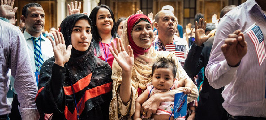 New U.S. citizen Mosammat Rasheda Akter, originally from Bangladesh, holds her 7-month-old daughter, Fahmida, as she recites the oath of allegiance during a naturalization ceremony at the New York Public Library on July 3 in New York City. (photo: Drew Angerer/Getty)