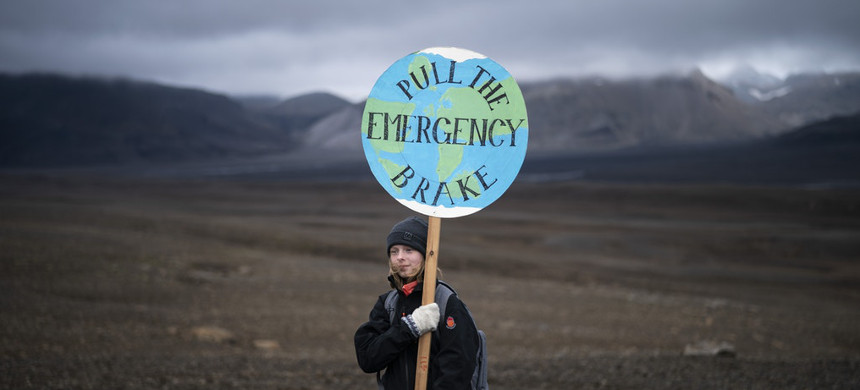 A girl holds a sign that reads 'pull the emergency brake' at a ceremony to commemorate the Okjökull glacier in Iceland, on Aug. 18,