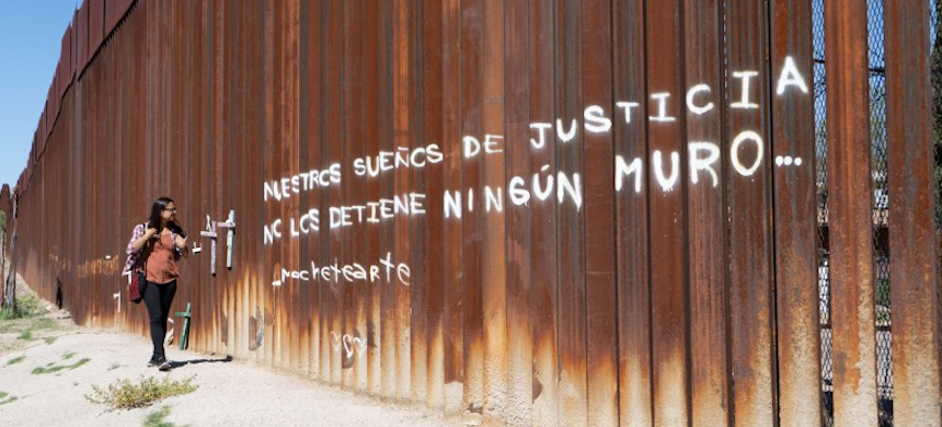 The Mexico side of the border wall with graffiti reading: