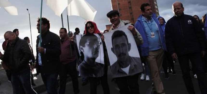 People hold posters with photographs of murdered Colombian social leaders in Bogota, Colombia July 26, 2019. (photo: Reuters)