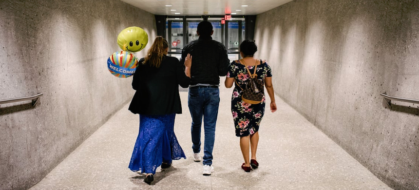 Marta and her daughter Julia walk out of the airport with her son José, who is developmentally delayed, after her arrived at Dulles international airport in Virginia. (photo: Jason Andrew/Guardian UK)