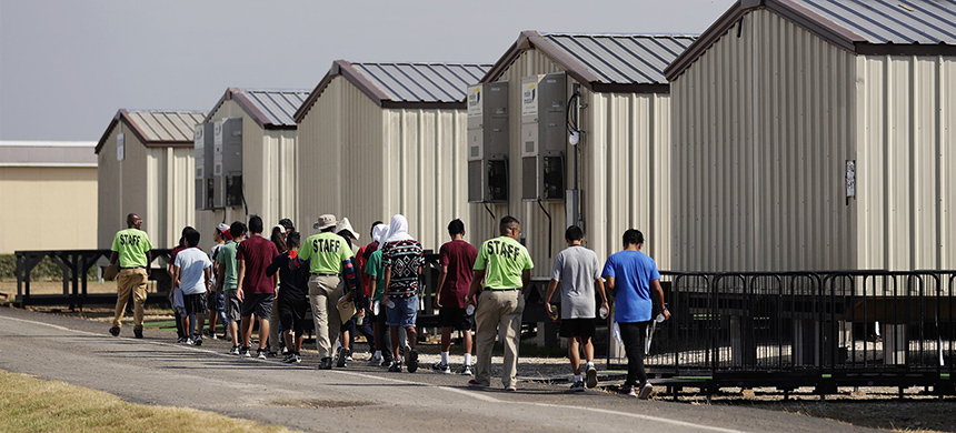 Staff escort immigrants to class at the U.S. government's holding center for migrant children in Carrizo Springs, Texas, on July 9, 2019. (photo: Eric Gay/AP)