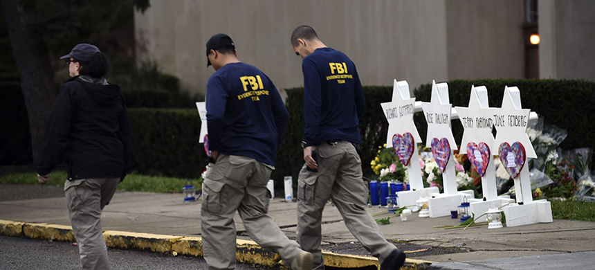 FBI agents walk past a memorial outside the Tree of Life synagogue in Pittsburgh after a shooting there in October. (photo: Brendan Smialowski/AFP/Getty Images)