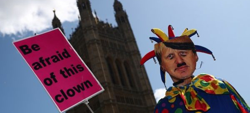 An anti-Brexit protester wearing a clown costume and a defaced mask depicting British Prime Minister Boris Johnson holds a placard outside the Houses of the Parliament in London, Britain, September 4, 2019. (photo: Reuters)