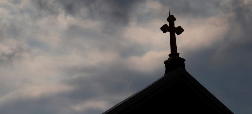 Storm clouds pass over a Roman Catholic church. (photo: Jason Cohn/Reuters)